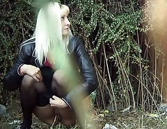 Blonde in pantyhose and jacket pissing